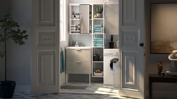 Vita dörrar står öppna till ett litet badrum med vita smala hyllor mellan ett vitt tvättställ och en tvättmaskin.