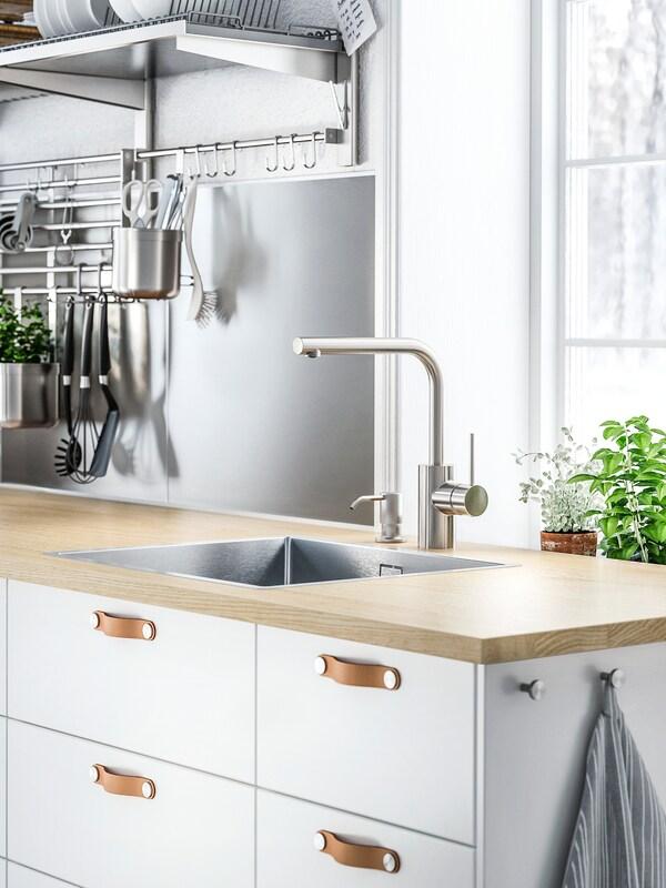 Vita skåp med vita lådfronter och ÖSTERNÄS läderhandtag under en bänkskiva i trä med diskho och köksblandare.