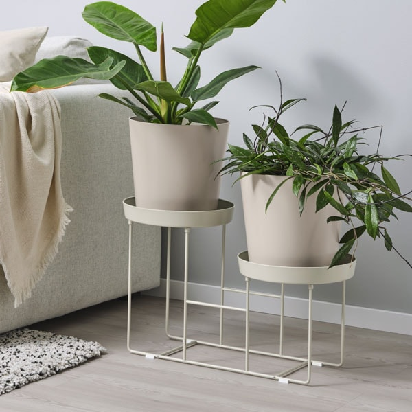 VITLÖK plant stand with two plants, placed by a beige sofa.