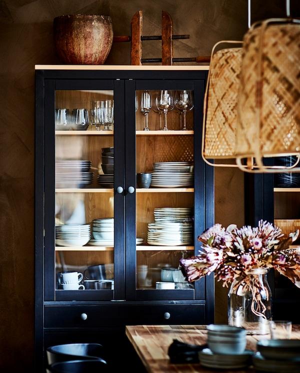Vitrina s posuđem i čašama, dve visilice od bambusa i trpezarijski sto od bagrema.