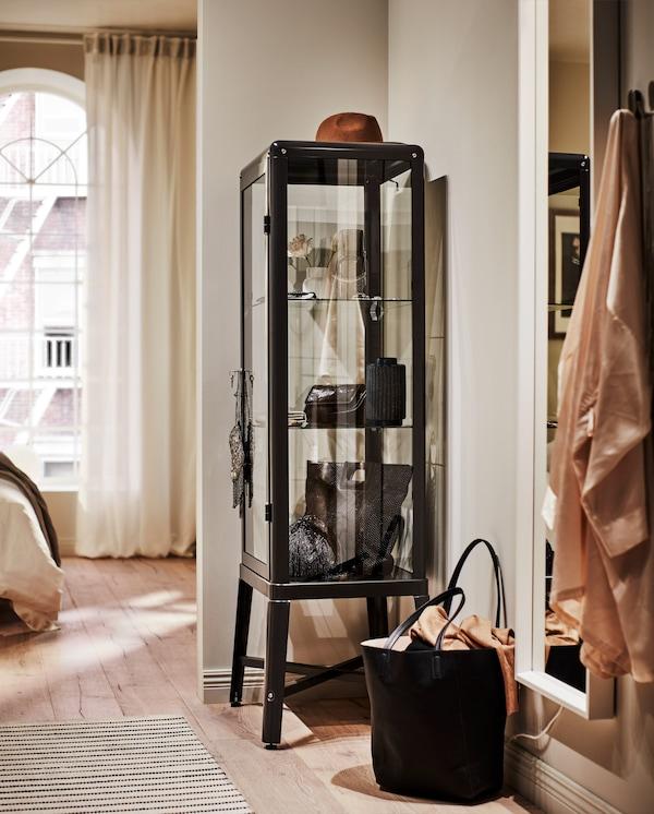 Vitrine à cadre gris foncé placée dans un coin où sont rangés et exposés de belles chaussures et accessoires.