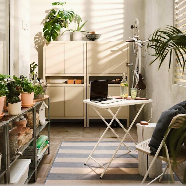 Vitt utomhusbord med dator, fyra beige stålskåp, diverse växter och en vit cykel som hänger på väggen.