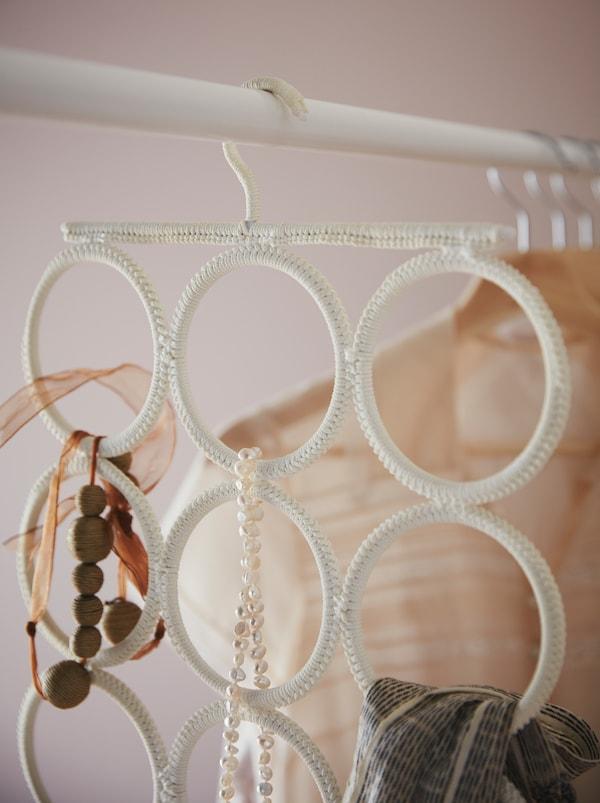 Von einer Kleiderstange hängt ein KOMPLEMENT Aufhänger, an dem ein Schal und ein paar Accessoires befestigt sind.