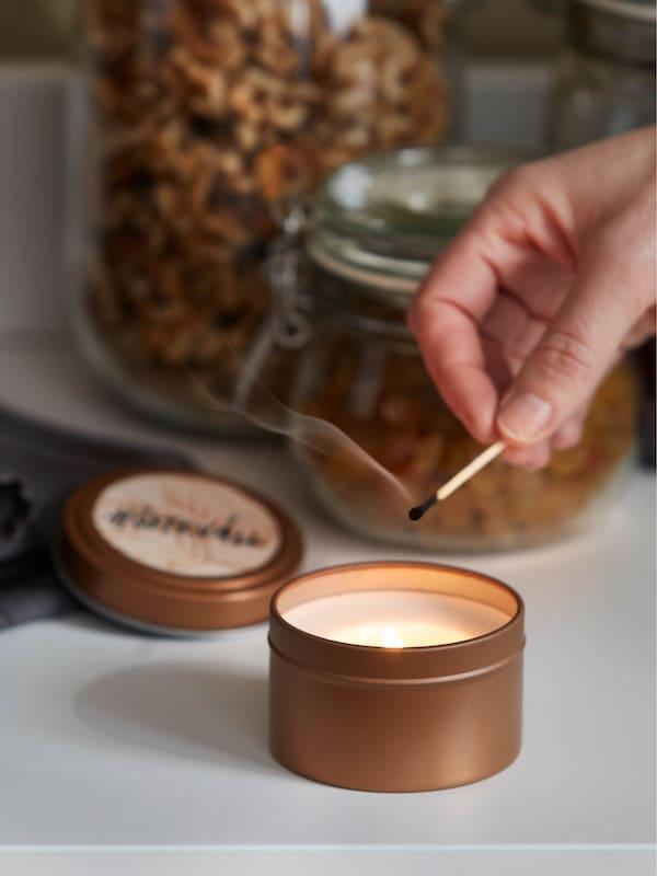 Vonná sviečka v plechovke HÖSTKVÄLL na bielom príborníku HAUGA, v pozadí stojí sklená dóza KORKEN s hrozienkami a orechmi.