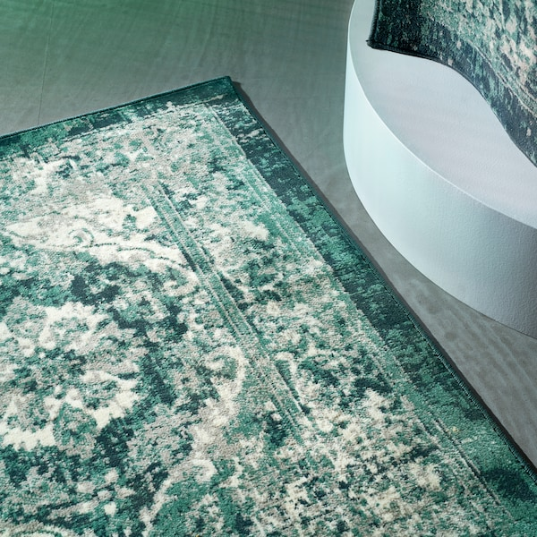 빈티지한 그린 색상의 VONSBÄK 본스베크 러그가 그레이그린 톤의 바닥에 놓여 있는 모습