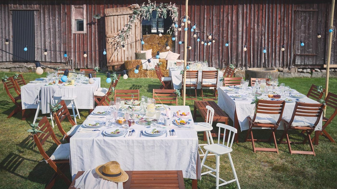 Vor einer Scheune sind im Freien Tische mit GULLMAJ Tischdecken, UPPLAGA Tellern, DYRGRIP Gläsern und UPPHÖJD Besteck für eine Feier gedeckt.