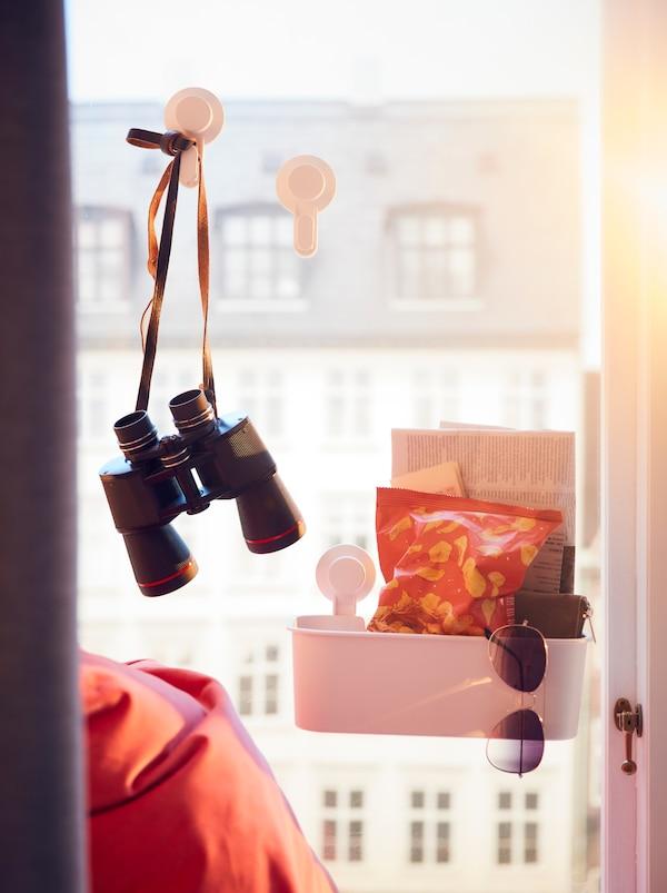Vor Gebäudefassaden ist ein Fenster mit einem TISKEN Haken mit Saugnapf zu sehen, an dem ein Fernglas hängt, und ein TISKEN Korb mit Saugnapf für Sonnenbrille und Co.