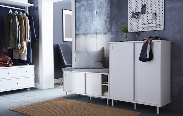 Vorzimmer mit vier braunen Fußmatten, einer ELVARLI Kombination mit Schubladen und Kleiderstange, zwei Schuhschränke wovon eine als Sitzbank dient.
