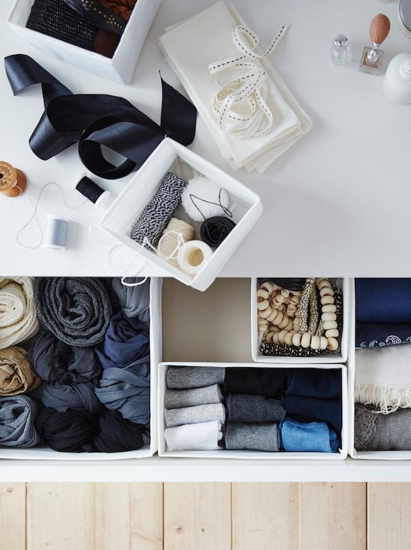 Vrh komode s fiokama, s dodacima za šivenje. Otvorena fioka s odećom lepo složenom u SKUBB kutije.