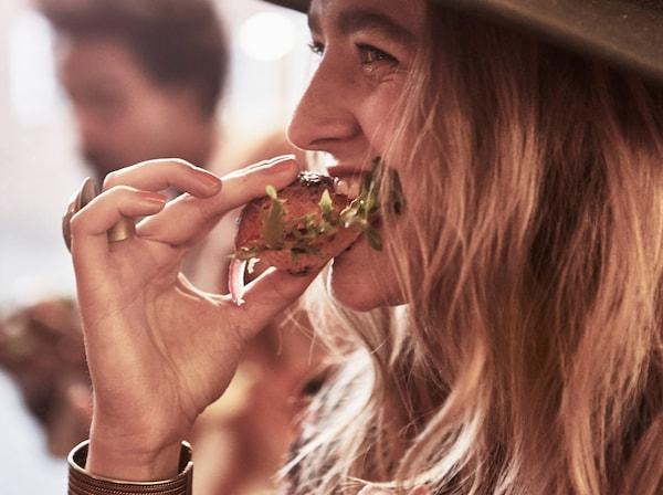 Vrouw eet een broodje met salade