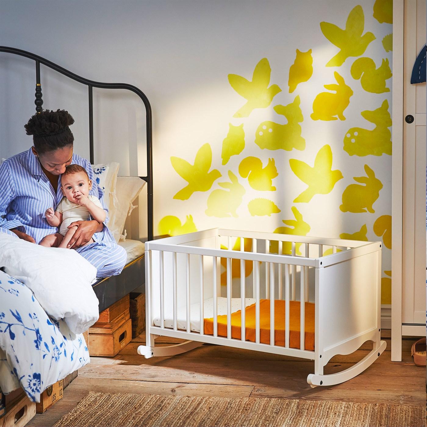 Vrouw en baby zitten op bed naast een witte houten SOLGUL wieg met ronde spijlen en afgeronde randen.