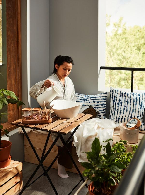 Vrouw gekleed in een badjas zittend op een balkon. Ze giet water in een SKYN serveerschaal met SAXBORGA toiletaccessoires eromheen.