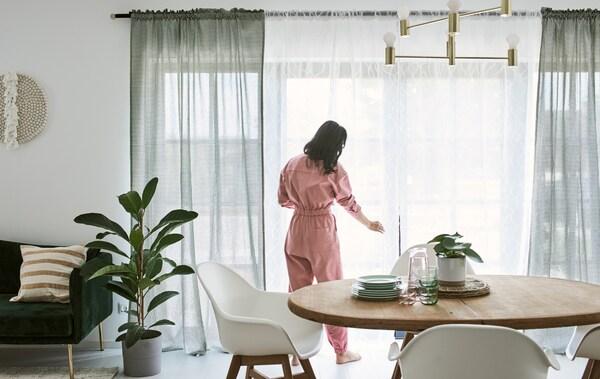 Vrouw in een roze jumpsuit prutst wat aan de gordijnen van schuiframen in een eetkamer met een houten eettafel en witte stoelen.