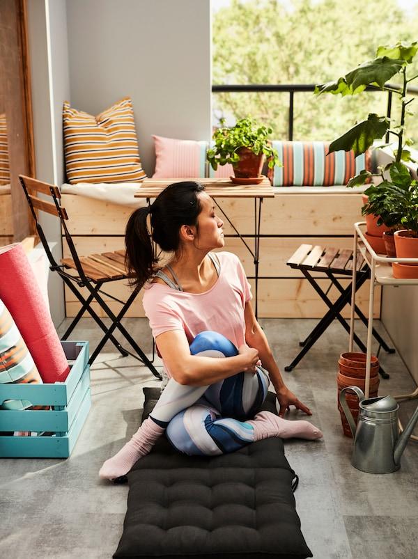 Vrouw in een yogahouding zit op een HÅLLÖ ligbedkussen dat is uitgespreid op de vloer van een zonovergoten balkon.