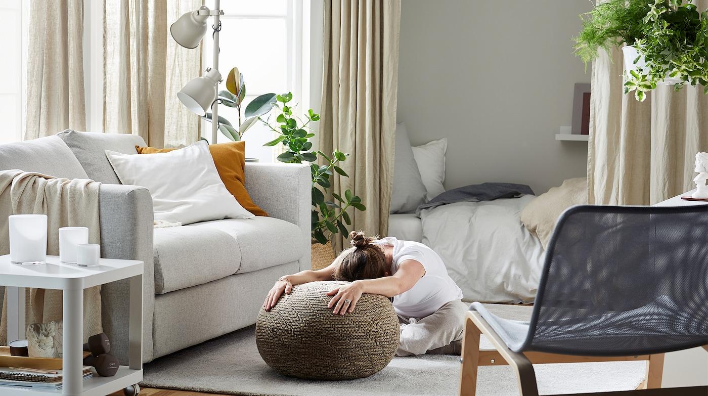 Vrouw zit op een tapijt in de woonkamer, op haar knieën en voorovergebogen, met haar uitgestrekte armen op een poef.