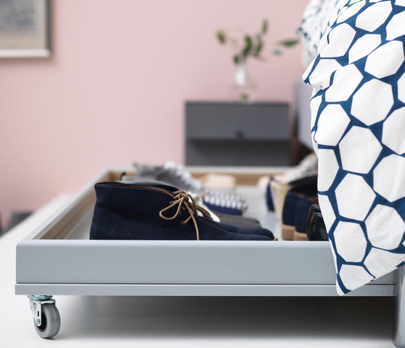 Vue de côté d'une boîte sur roulettes sortant de sa cachette en dessous du lit.