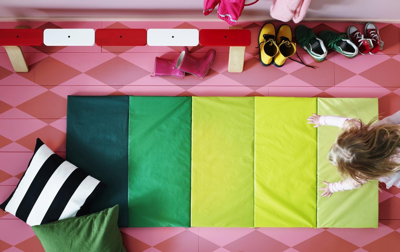 Vue de dessus d'un tapis de jeu rayé vert sur un sol rose avec un enfant qui joue.