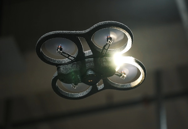 Vue en contre-plongée d'un grand drone dans un entrepôt sombre.