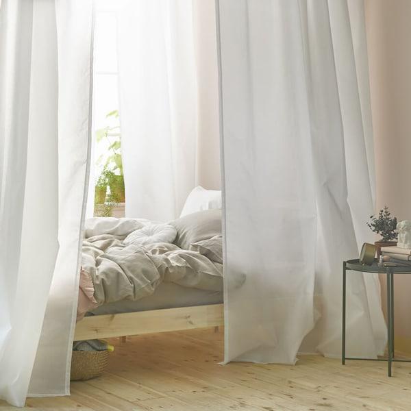 Vuodekatos makuuhuoneessa luo yksityisyyttä ja säätelee valon määrää. Valkoinen kevyt VIVAN-verho ja kattoon asennettava kiskojärjestelmä toimivat vuodekatoksena.