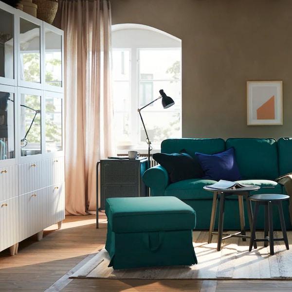 Výřez obývacího pokoje kde je detail na sedací soupravu a vitrínu.