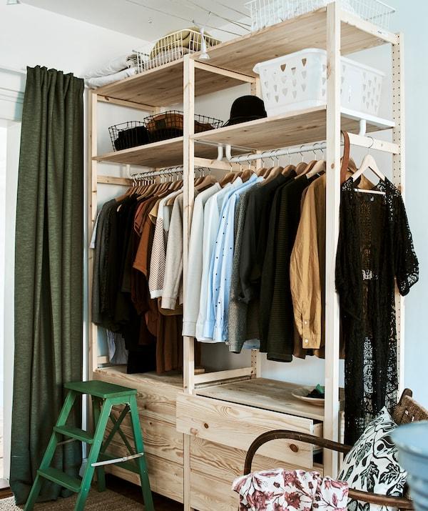 Высокий деревянный модуль для хранения одежды с выдвижными ящиками, платяной штангой и полками с коробками. В углу стоит зеленый табурет-лестница.