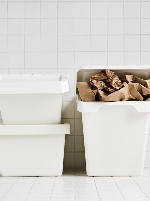 W pokoju wyłożonym białymi płytkami trzy białe kosze SORTERA, z których jeden jest wypełniony brązowym papierem.