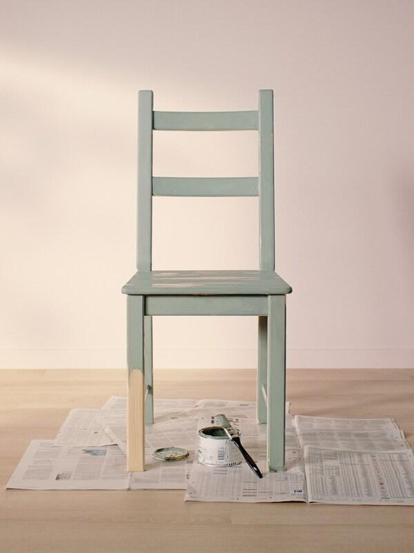 W pustym pokoju z jasną drewnianą podłogą i jasnoróżowymi ścianami na starych gazetach stoi krzesło IVAR w kolorze jasnozielonym.
