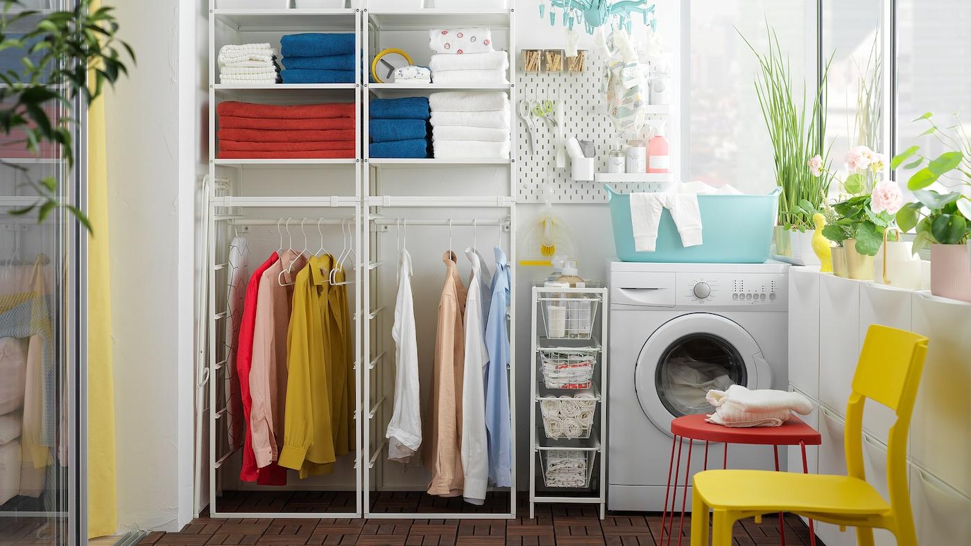 Wäschezimmer im Wintergarten mit Handtüchern und Kleidung auf einem weißen JONAXEL Regal, daneben ist eine Waschmaschine zu sehen.