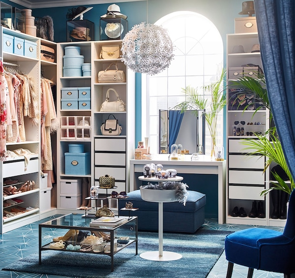 Walk-in closet furnished with PAX white wardrobe storage series, and deep blue hues.