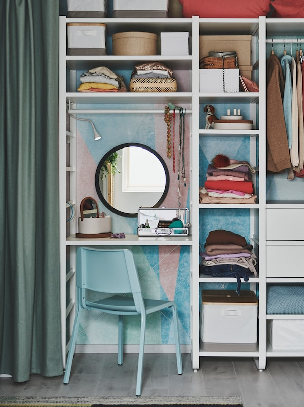 Wall-covering shelving unit used as wardrobe, part of it acting as dressing table, with mirror, a TEODORES chair and make-up.