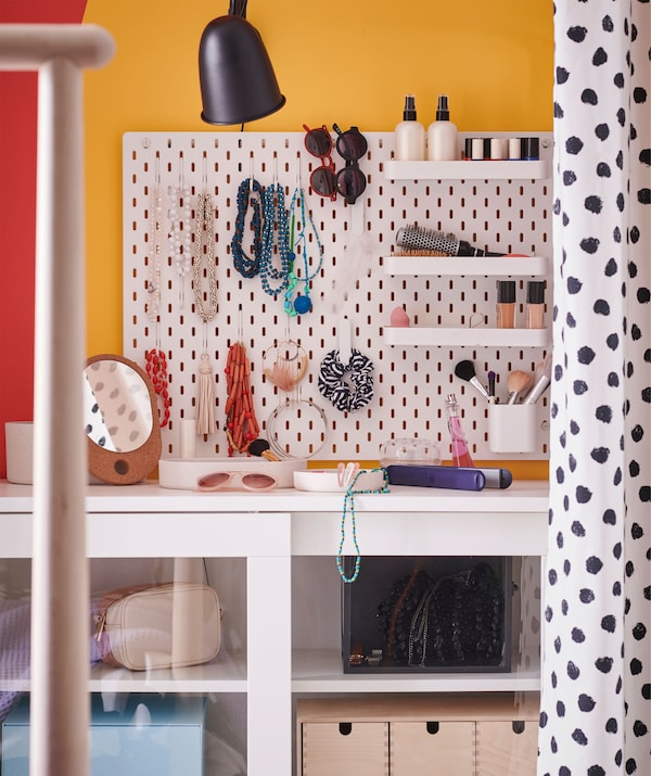 Wall-mounted pegboard with a variety of hooks and small shelves holding necklaces, bracelets, sunglasses and cosmetics.