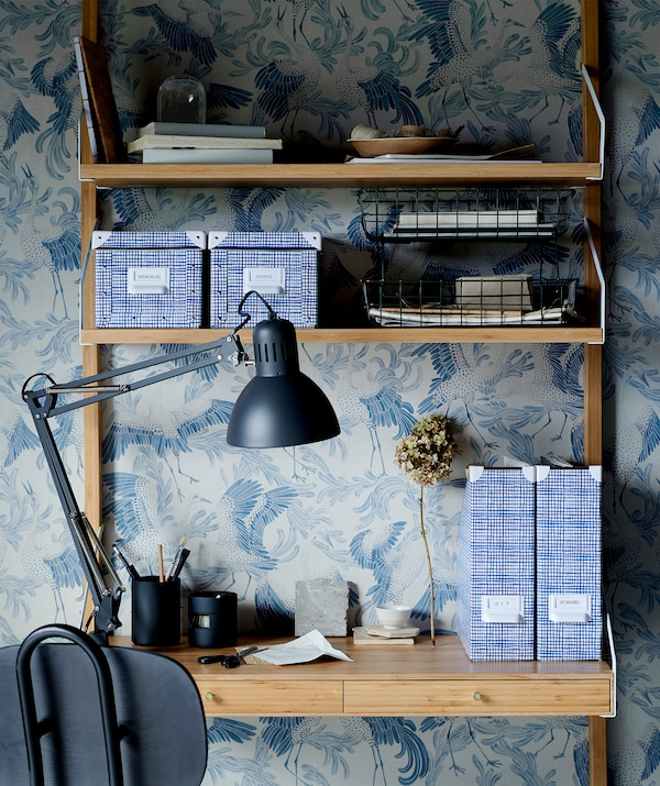 Wall-mounted shelving doubling as a small home office; various storage, desk lamp, office chair, graphic-patterned wallpaper.