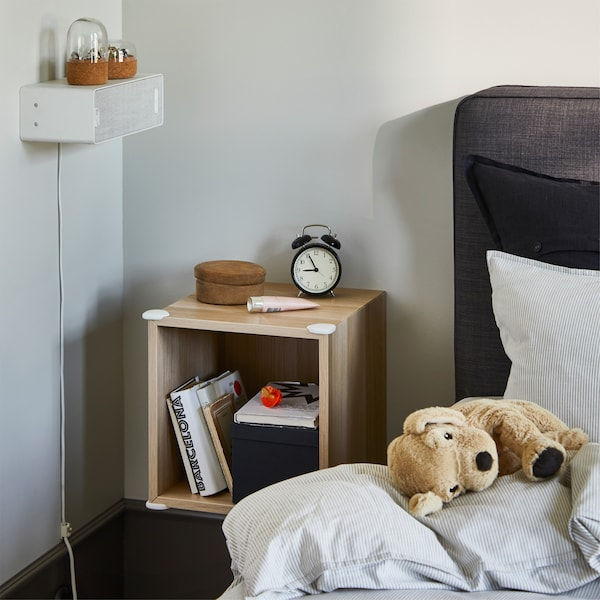 Wall-mounted shelving unit with white corner bumpers on the edges that keep children safe when crawling up and down the bed.