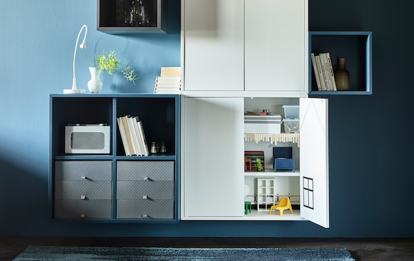 Wall-mounted storage cabinets in a modern, grown-up living room hide a secret play station for children.