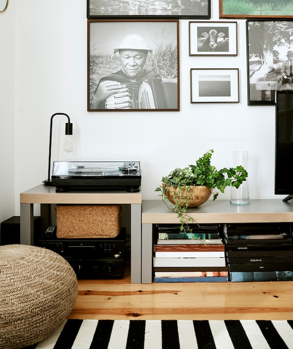Wall of black and white photos above two low benches, one has a record player, the other has stacks of books beneath it.