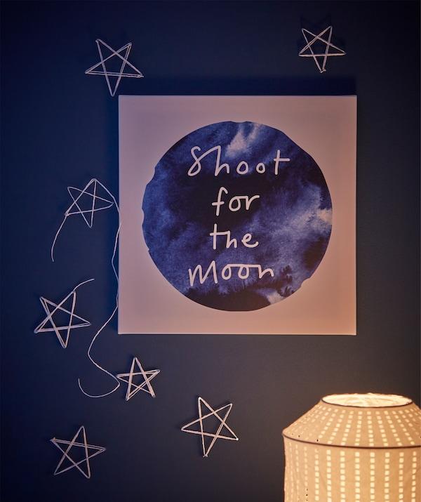 Wall section above desk, adorned with moon-themed PJÄTTERYD picture art and stars formed by tacks and ribbon.