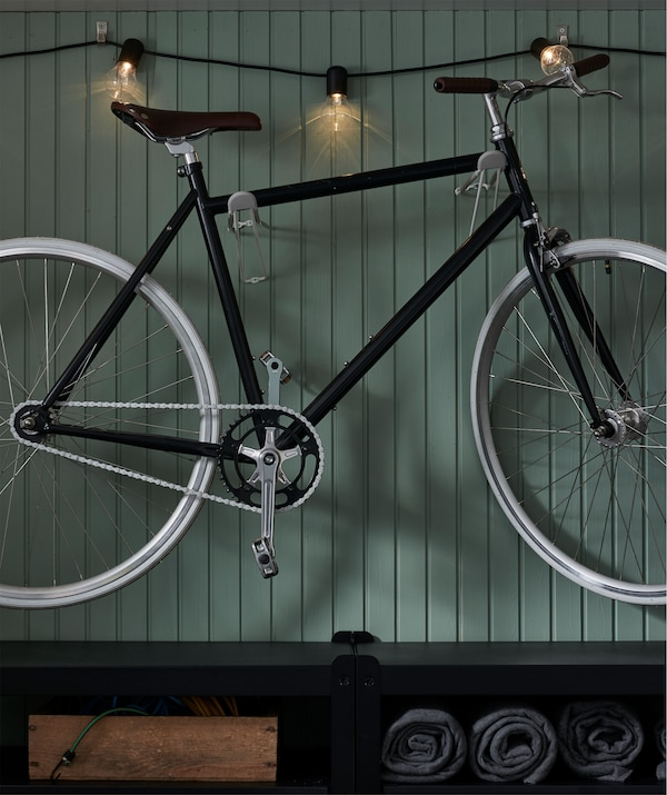 Wall section with a bike mounted on hooks and lit with a lighting chain running along the wall. A shelving unit sits below.