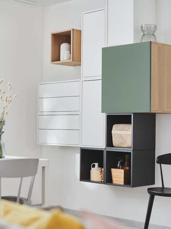 Wall section with EKET shelving units combined with other storage units, creating a deliberately irregular yet geometric look.