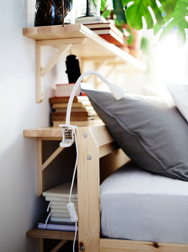 Wall shelves fill the space between a wall and the head end of a bed, creating a combination of storage and bedside table.