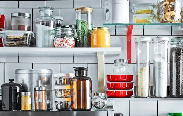 Wall shelves mounted on white tiles store this kitchen's most used ingredients in jars and containers.