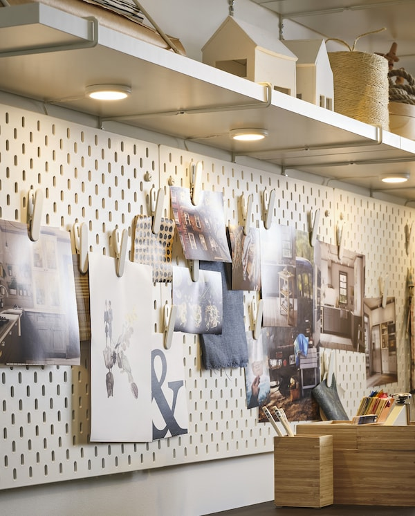 Wall shelves with white LED spotlights attached on their underside: they illuminate pictures and posters on white pegboards.