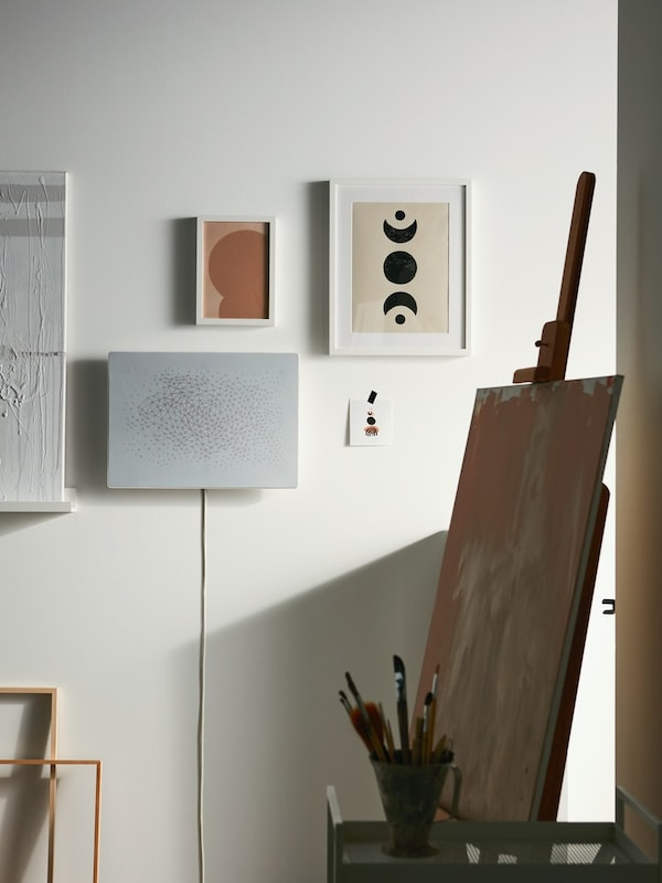 Wall with a collection of art prints in frames and SYMFONISK speaker frame. Art easle sits in the fore ground