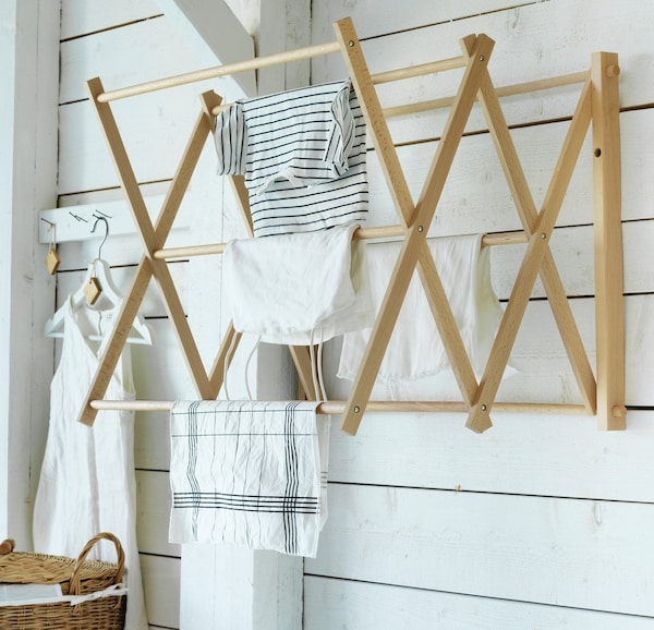 Wandbefestiger Wäscheständer aus Holz mit Putztüchern daran häängend.