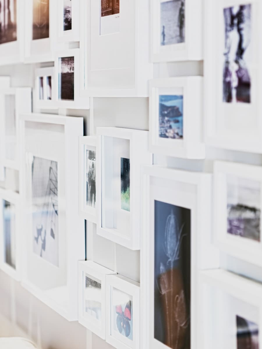 Wandgalerie mit Fotos in weißen Bilderrahmen