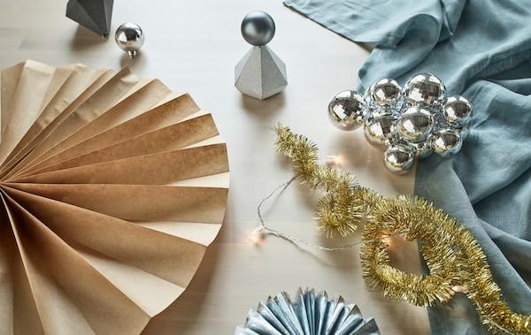 Wandversiering, tafeldecoratie en papieren rozetten gemaakt van gerecycleerde feestversiering zoals zilverkleurige geschenkdoosjes, kerstballen en cadeaupapier.