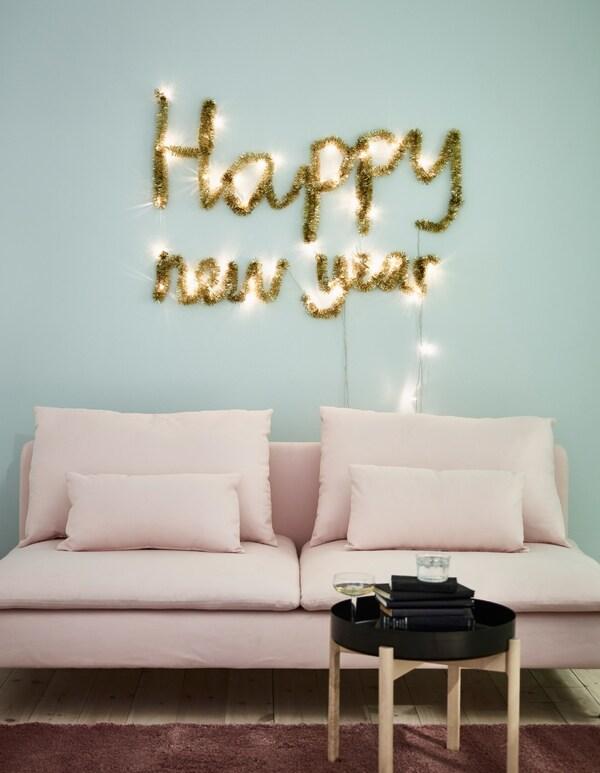 Wandversiering voor Nieuwjaar gemaakt van SÄRDAL ledlichtsnoeren op batterijen en een goudkleurige slinger, boven een roze zitbank.