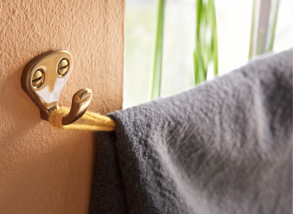 Want both privacy and some daylight? Fold a throw over a horizontal fabric ribbon that you attach to hooks. IKEA offers a wide range of smart hooks such as IKEA KVASP hook in brass-colour.