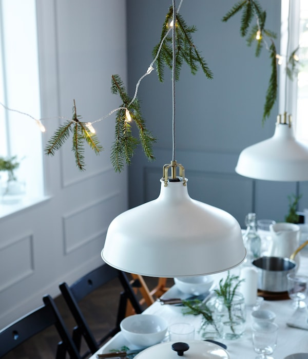 Want to win a few wows with your table setting? Decorating above the table helps make a super cosy and intimate celebration. We've used hanging lights and pine branches.