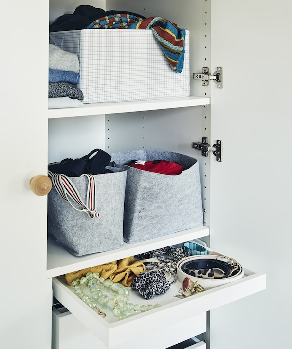 Wardrobe shelves filled with baskets, boxes and folded clothes, plus a drawer of accessories.