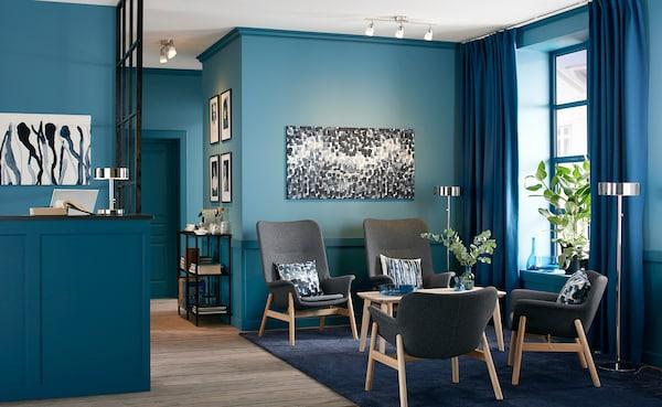 Wartebereich für Gäste in blau mit 4 VEDBO Sesseln, einem LISABO Tisch, Wandbildern & Pflanzen.